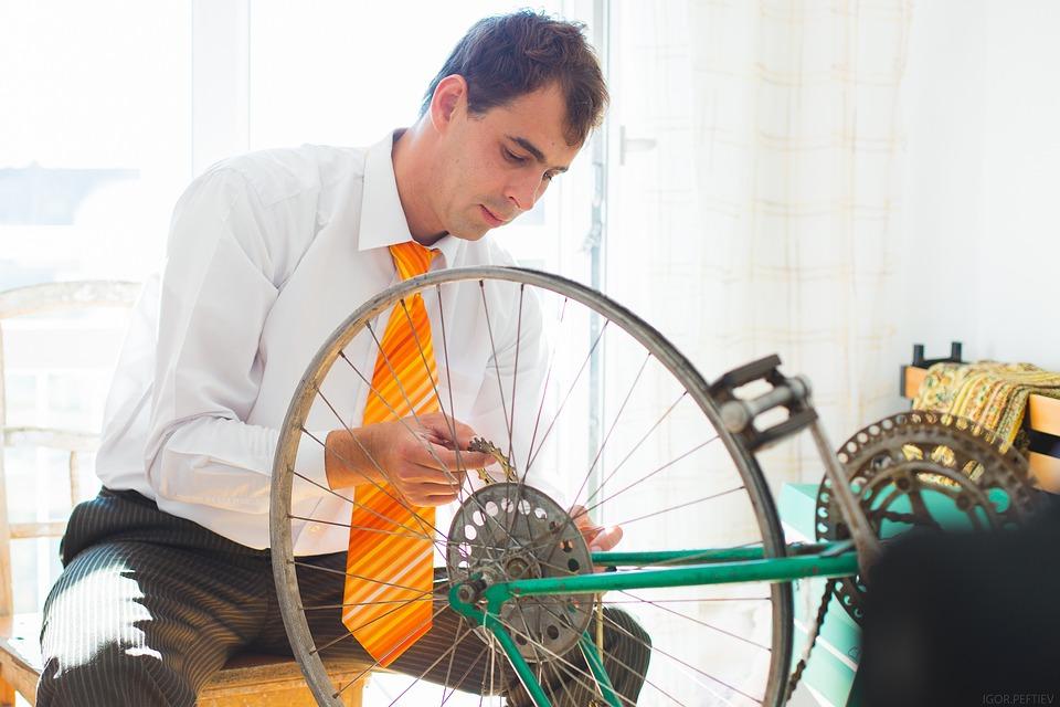 自転車のホイールを見る男性